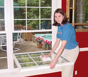 Capital Remodeling Worker Cleaning Replacement Window